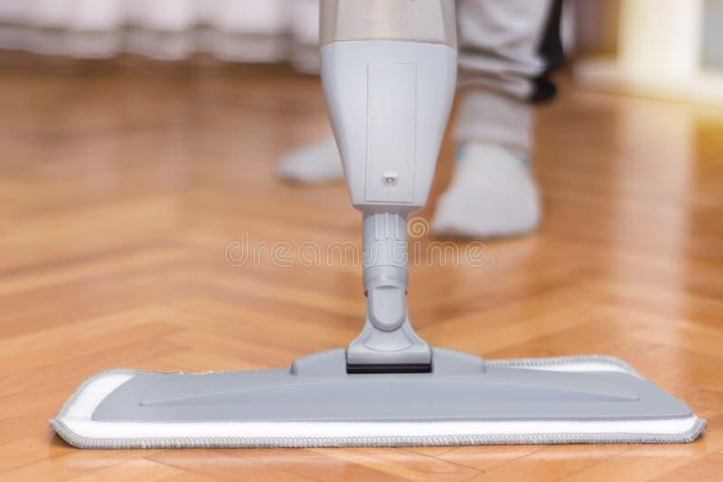 清洗地板木条地板的妇女与灰色拖把 免版税库存照片