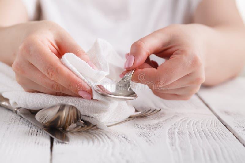 清洗多斑点的银器的女性手与清洁产品a 免版税库存照片