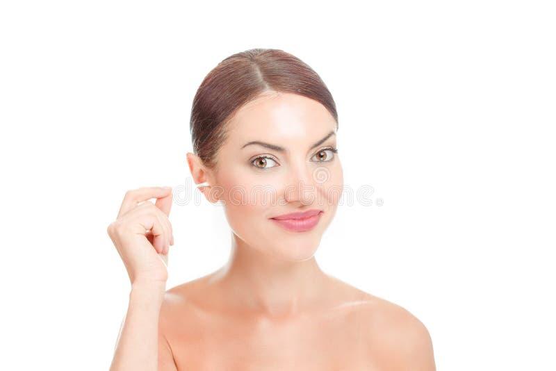 清洗她的耳朵的妇女与棉花芽 免版税库存照片