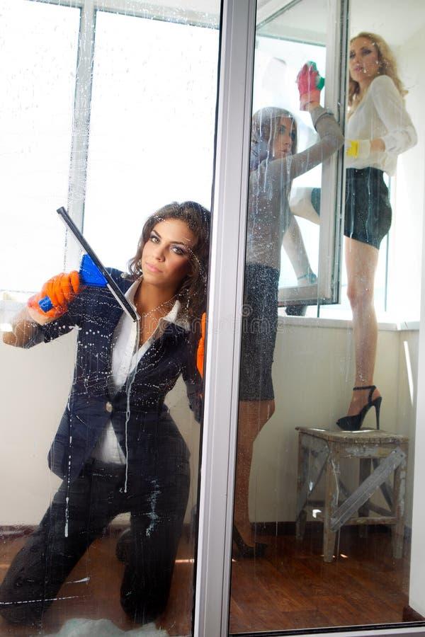 清洗她的视窗的妇女 库存照片