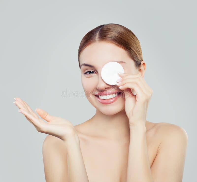 清洗她的面孔的可爱的妇女与化装棉 库存图片