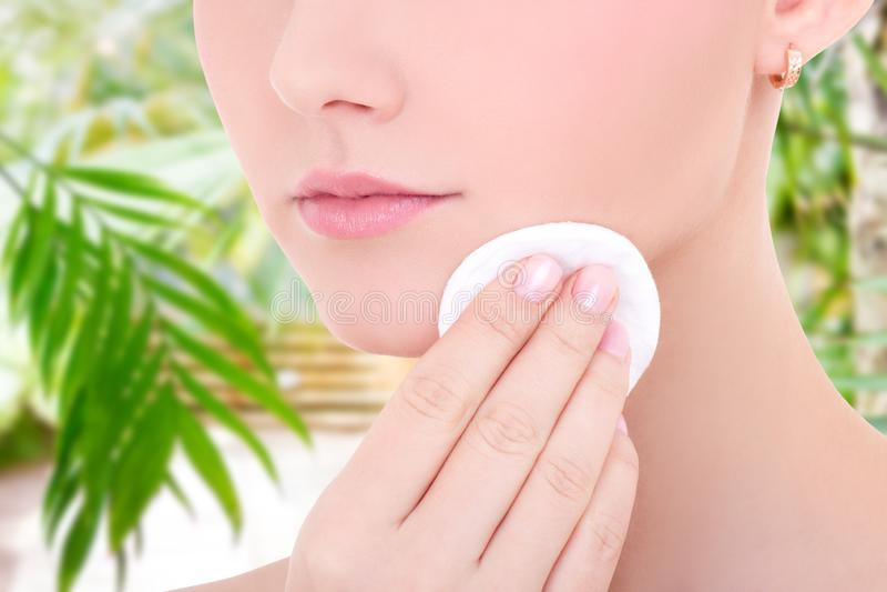 清洗她的面孔皮肤的年轻美女接近的画象由化装棉 库存图片