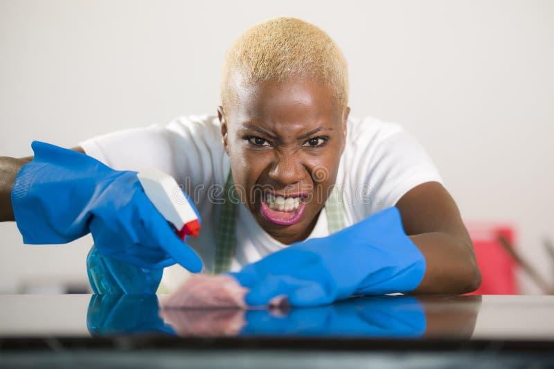 清洗家庭厨房的洗涤的橡胶手套的年轻可爱的被注重的和让烦恼的美国黑人的妇女疲倦了并且劳累了过度i 免版税库存照片