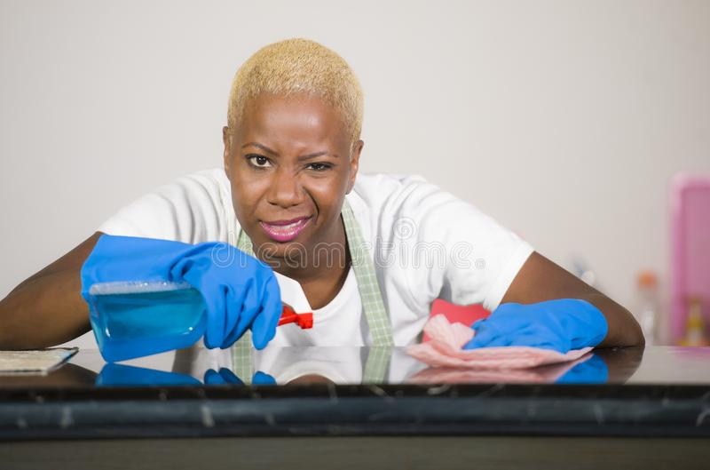 清洗家庭厨房的洗涤的橡胶手套的年轻可爱的被注重的和让烦恼的美国黑人的妇女疲倦了并且劳累了过度i 免版税库存图片