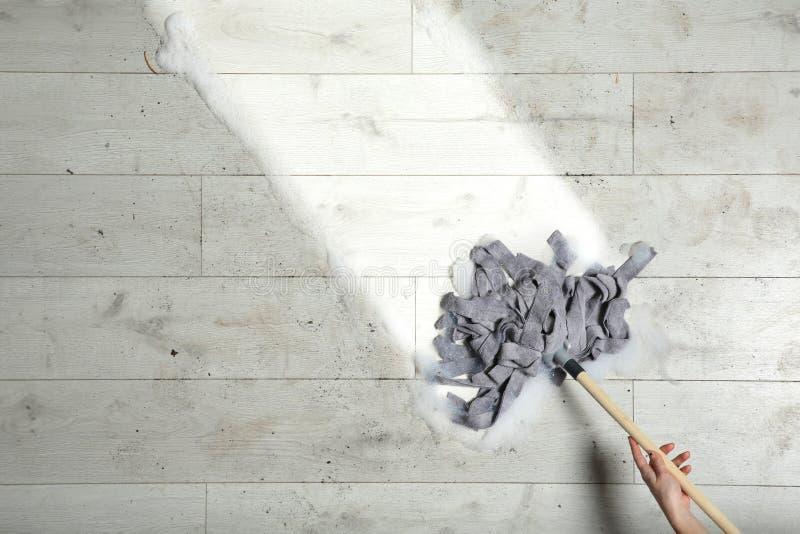 清洗木地板的妇女与拖把,顶视图 免版税库存图片