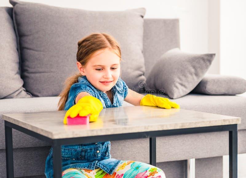 清洗木桌的女孩 库存图片
