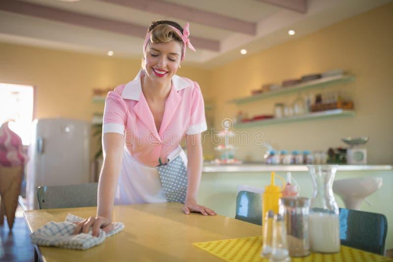 清洗桌的女服务员在餐馆 库存照片