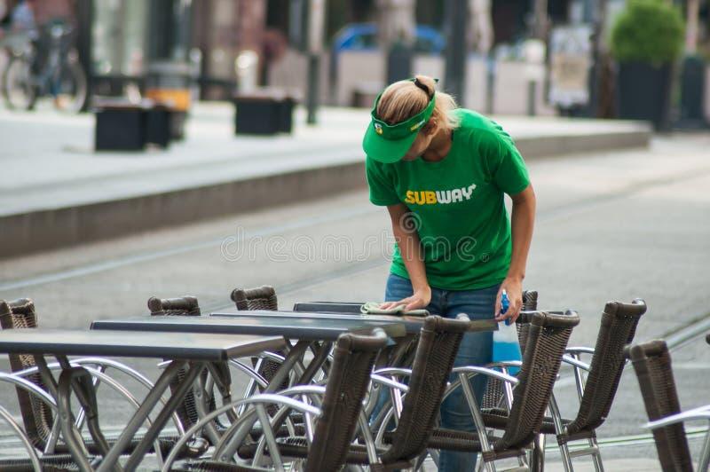清洗桌的女服务员画象在地铁便当餐馆 免版税库存照片