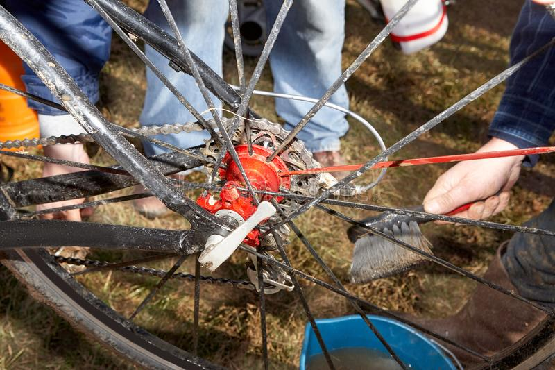 清洗泥泞的自行车轮幅的手 图库摄影
