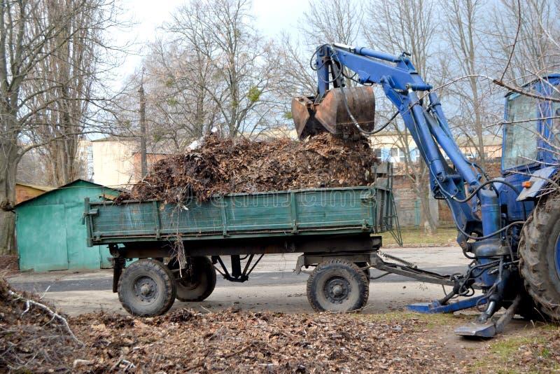 清洗的干燥分支和草在装载入卡车拖车的城市街道上 免版税库存图片