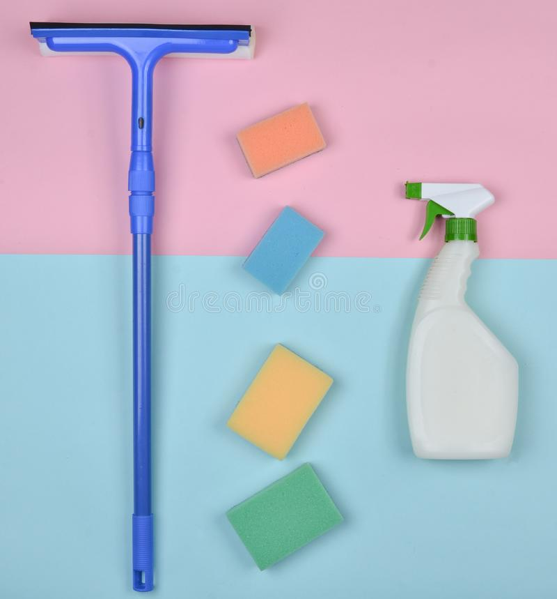清洗的玻璃窗的产品 海绵,窗口拖把,在蓝色桃红色淡色背景的喷水隆头清洁剂 库存照片