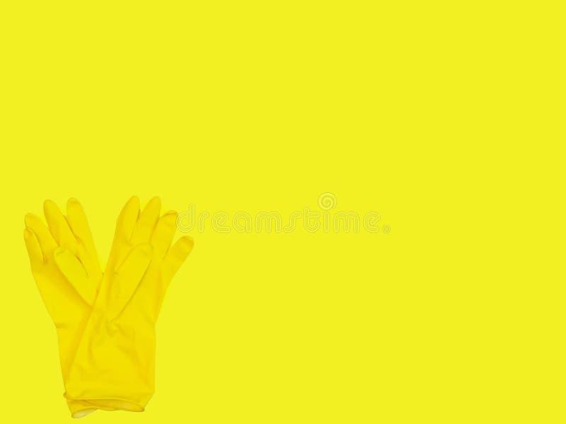 E 清洗的黄色橡胶手套在黄色背景 r 商业清洁 免版税库存照片