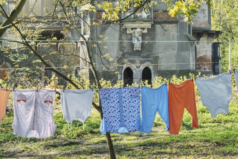 清洗破坏的内衣以一个老被破坏的宫殿为背景 免版税库存照片