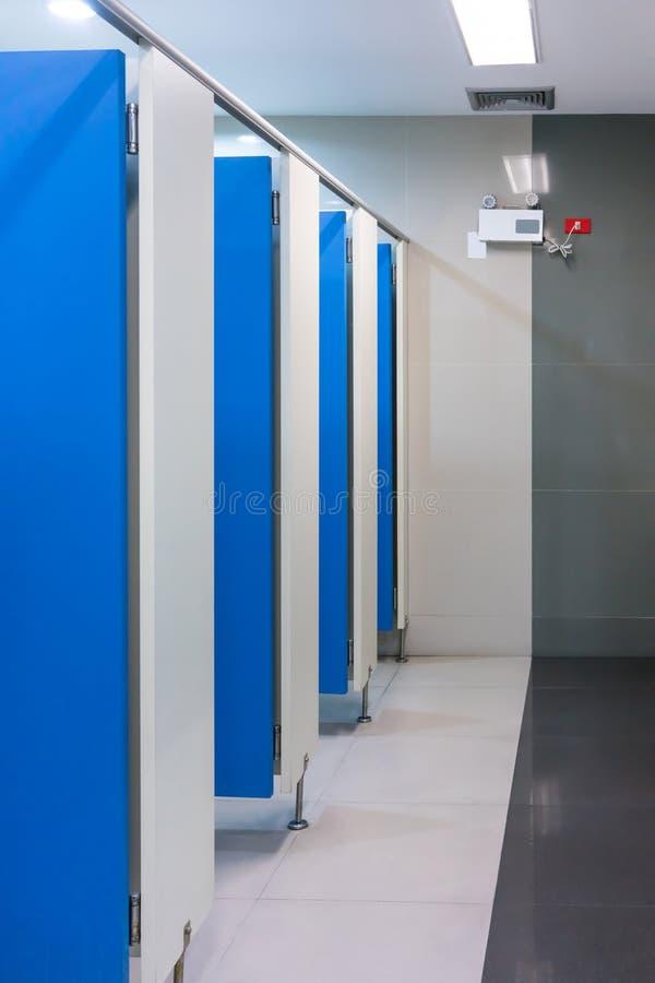 清洗空公共厕所的室与蓝色门 免版税库存照片