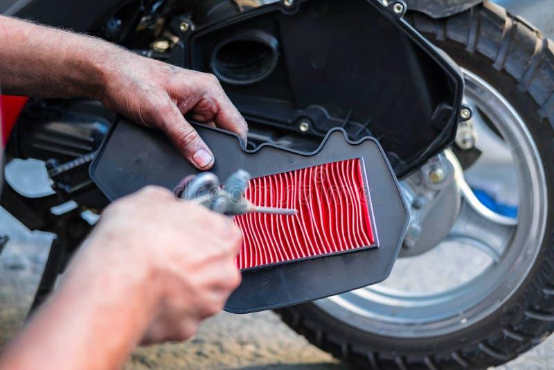 清洗空气过滤器、滑行车和摩托车, employee& x27; 在维护期间的s手 库存图片