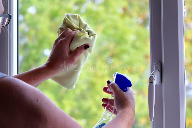清洗窗口的夫人在一个现代房子里 免版税库存图片