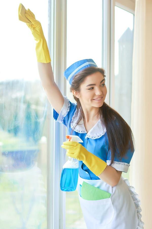 清洗窗口的快乐的佣人 免版税库存照片