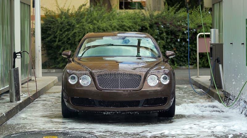 清洗站立在昂贵的洗车,优质自动服务的汽车 图库摄影