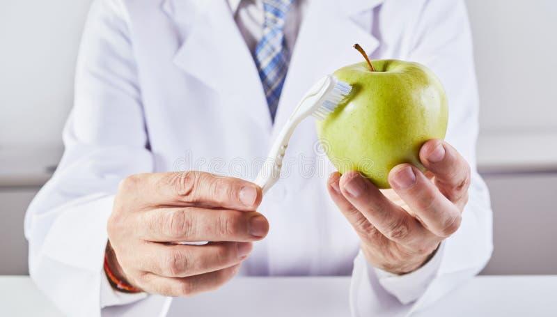 清洗绿色苹果的科学家与牙刷 免版税库存照片