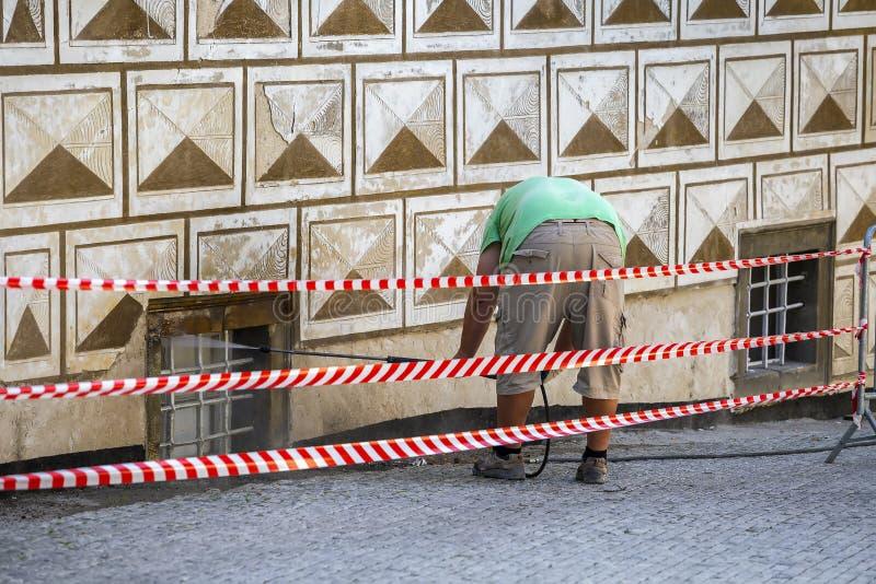 清洗肮脏的墙壁的工作者与高压喷水 免版税库存照片