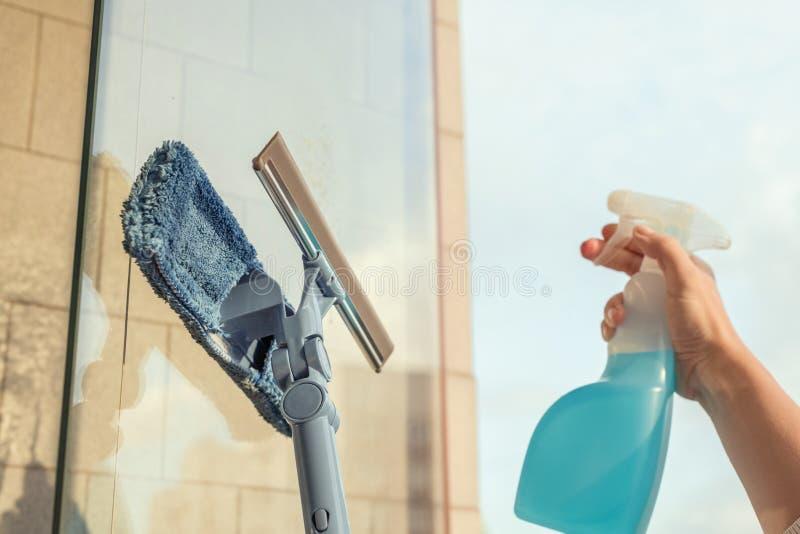 清洗阳台开窗口由喷洒的清洁产品和抹与拖把海绵的女孩夏天日落晚上 免版税库存图片