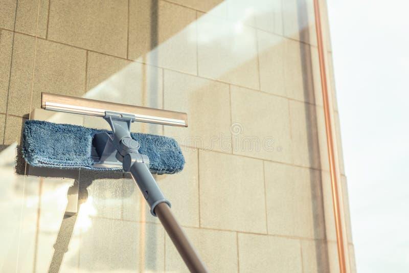 清洗阳台开窗口由喷洒的清洁产品和抹与拖把海绵的女孩夏天日落晚上 图库摄影