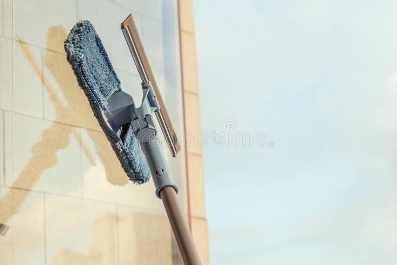 清洗阳台开窗口由喷洒的清洁产品和抹与拖把海绵的女孩夏天日落晚上 免版税库存照片
