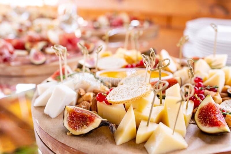 清淡的意大利快餐 在晚餐会的一张自助餐桌 乳酪盘子 在木桌上的可口乳酪混合 品尝盘 免版税图库摄影