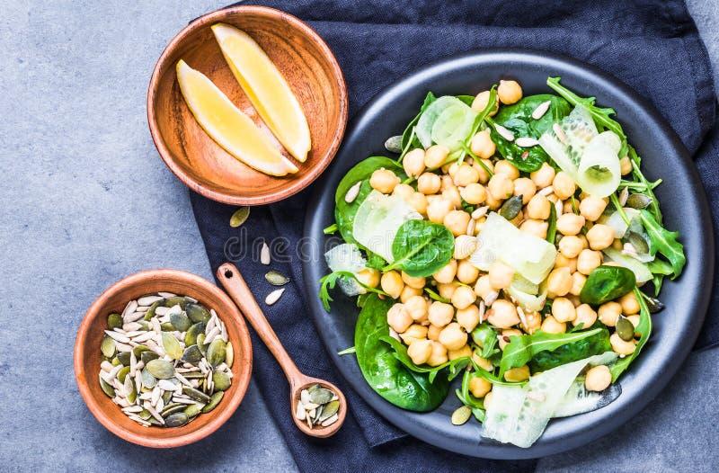 清淡的新鲜的沙拉用鸡豆和绿色,种子顶视图 素食主义者健康食物板材 免版税库存图片