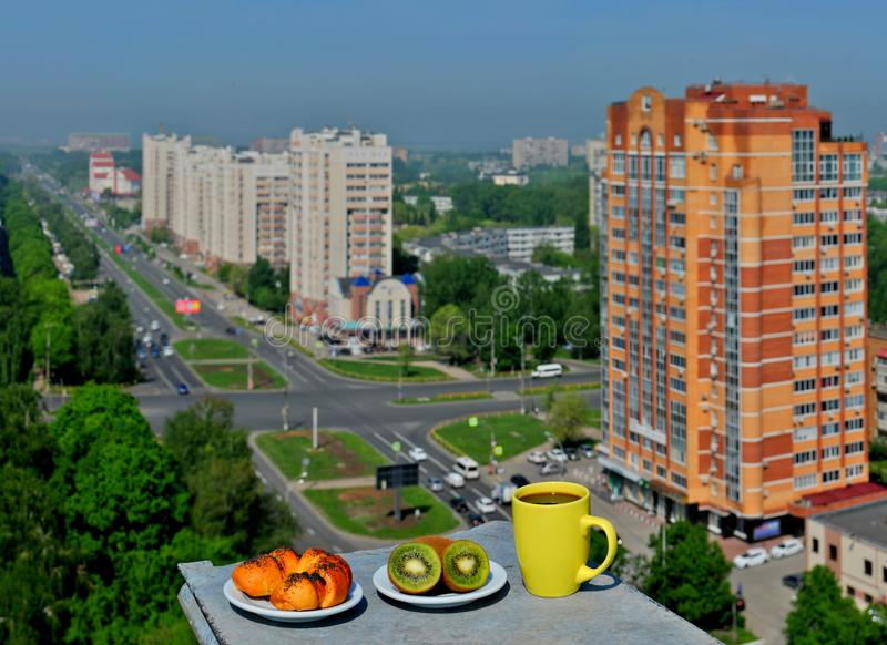 清淡的早餐有城市的一幅全景:与罂粟种子、两三个新鲜的猕猴桃和一个杯子的一个红润小圆面包咖啡 库存图片