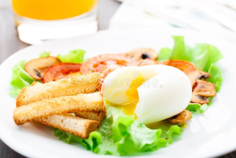 清淡的早餐用软蛋、蕃茄和油煎方型小面包片 库存照片