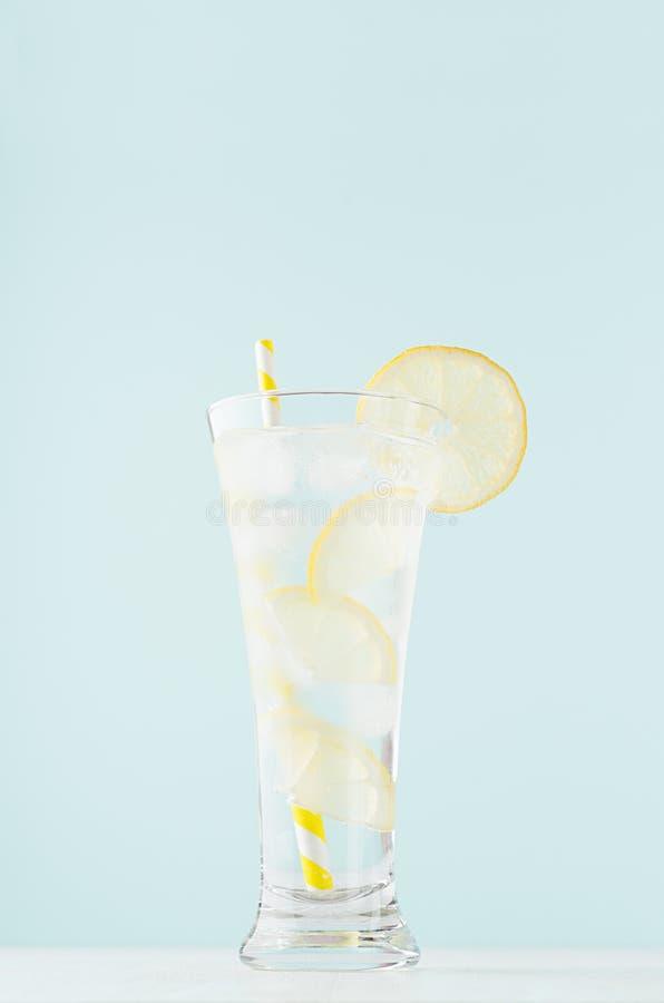 清爽的柠檬片、冰块、黄条稻草、白木桌上雅致的玻璃、薄荷色的排毒凉水 免版税库存照片