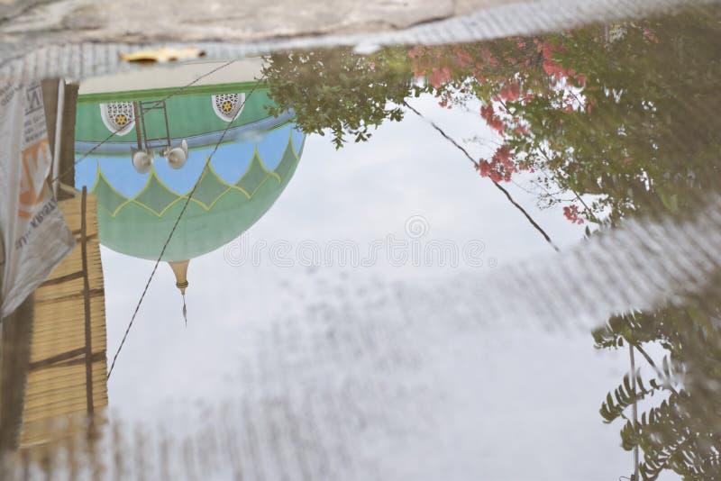 清真寺圆顶的反射在大雨以后的池塘 免版税库存照片