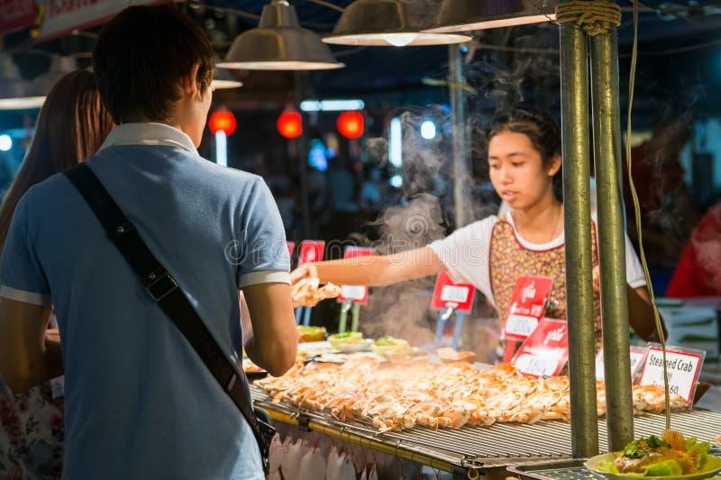 清迈,泰国-大约2015年8月:当地人民卖传统泰国食物和饮料在夜市场上在清迈, Thail 免版税库存照片