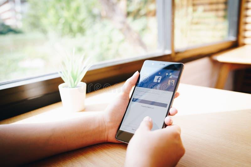 清迈,泰国- 1月22 :卡伦小山部落坐她的小屋在卡伦2010年1月22日的小山村庄在清迈,泰国 19,2019:举行有facebook应用程序的妇女华为在屏幕上 Facebook是一个普遍的自由社会媒介 库存照片