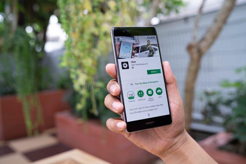 清迈,泰国- 8月05,2018 :拿着有Uber apps的人华为 Uber是智能手机app searc的运输网络 免版税图库摄影