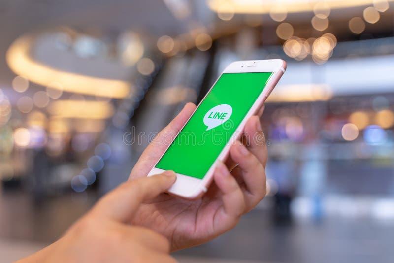 清迈,泰国- 5月 10,2019:拿着苹果计算机与线应用程序的妇女iPhone 6S罗斯金子在屏幕上 线是新的通信 库存图片