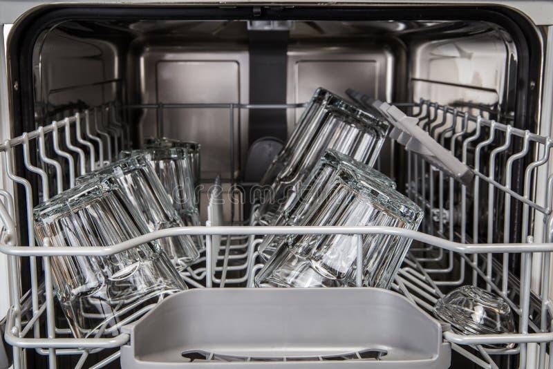 清洗在现代洗碗机机器的透明玻璃 免版税库存照片