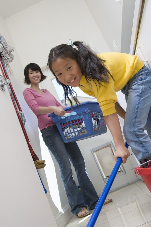 清洁地板的女儿帮助的母亲 图库摄影
