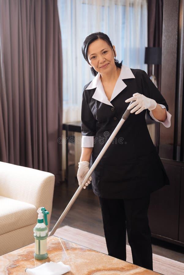 清洗地板的好严肃的旅馆佣人 库存图片