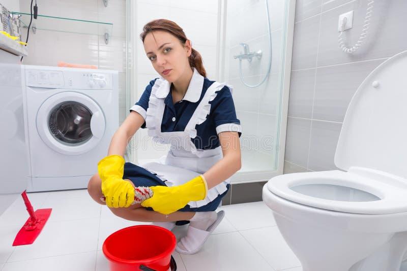 清洗地板的年轻管家或佣人 免版税库存图片
