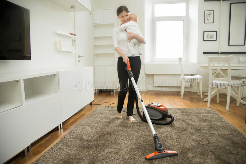 清洗地毯的愉快的微笑的妇女抱孩子 免版税库存照片