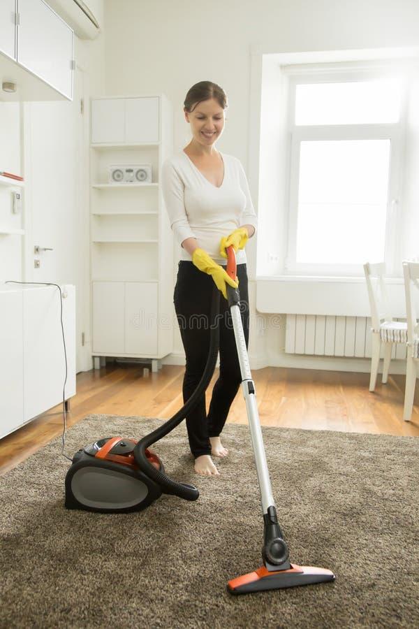 清洗地毯的愉快的微笑的妇女 免版税库存照片