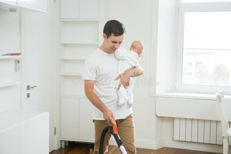 清洗地毯的沮丧的不喜欢出门的爸爸真空举行a 库存图片