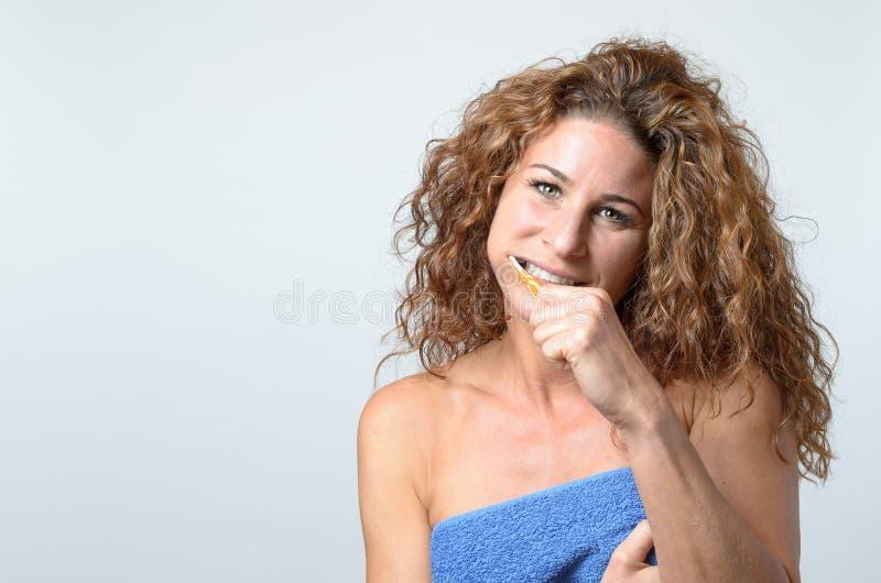 清洗她的牙的妇女与牙刷 免版税库存照片