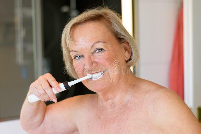清洗她的牙的年长露胸部的夫人 免版税图库摄影