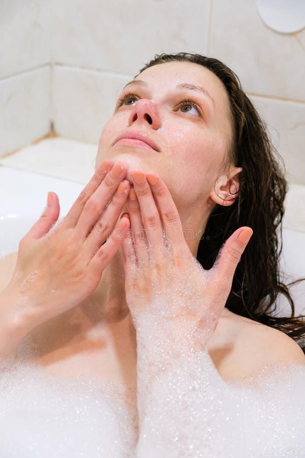 清洗她的面孔的美丽的妇女与在白色浴的泡沫治疗 免版税库存图片