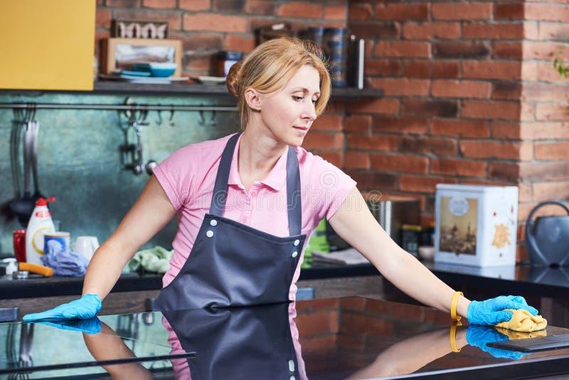 清洁服务 在厨房的妇女干净的烹饪器材 免版税库存照片
