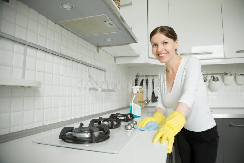 清洗火炉的年轻微笑的妇女佩带的橡胶手套 免版税库存图片