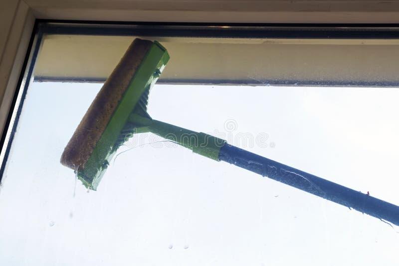清洗玻璃与橡皮刮板 免版税图库摄影